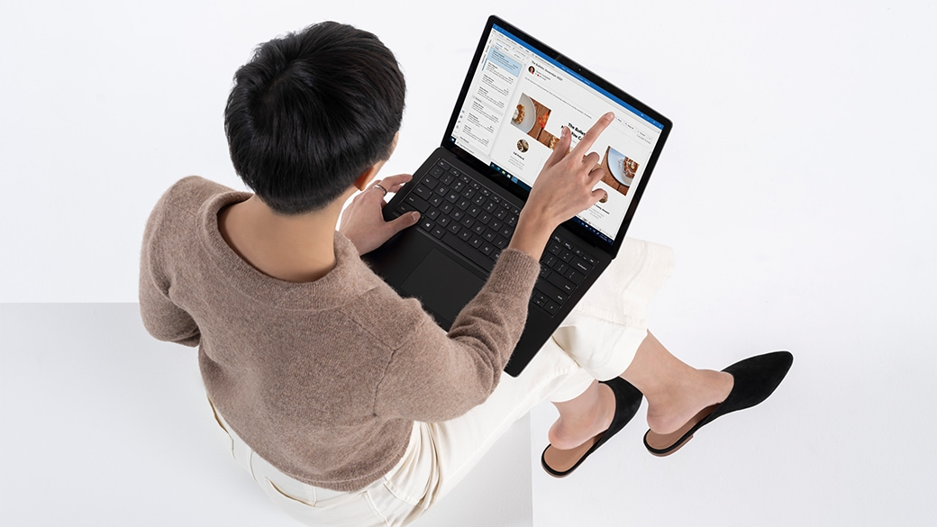 Person seated working with Surface Laptop 4 for Business on lap.