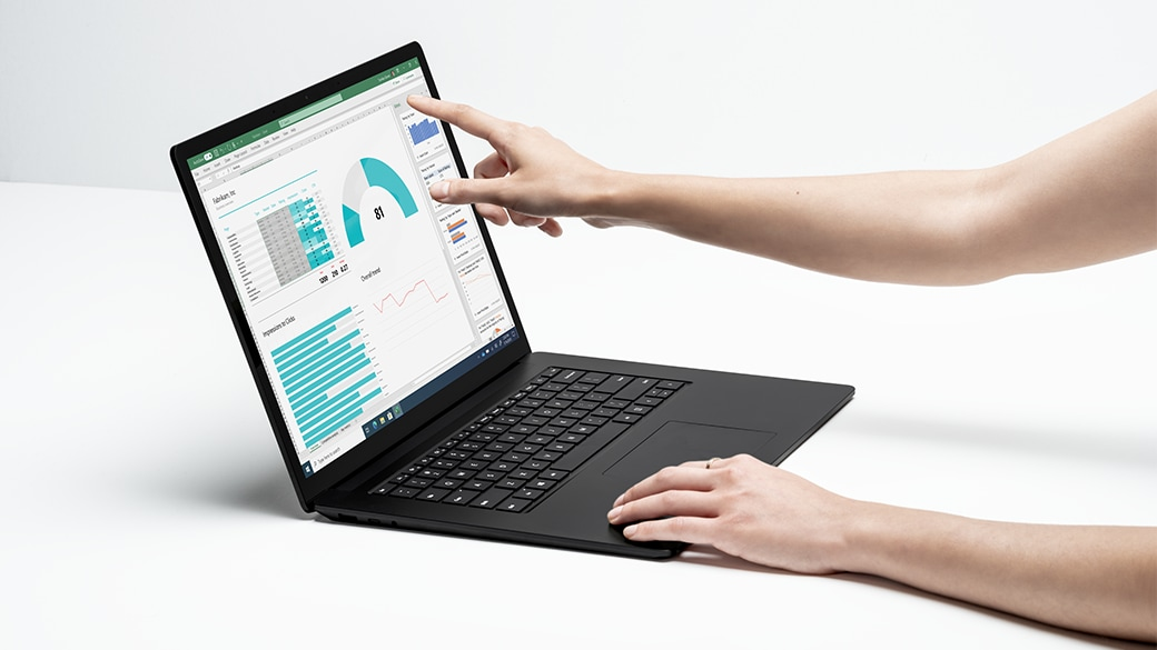 A person's hands working with Surface Laptop 4, one on the keyboard, the other touching the screen.