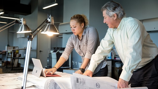Two people looking over a desk with a tablet on it.