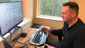 Phil Suver sits at his desk and looks at his laptop.