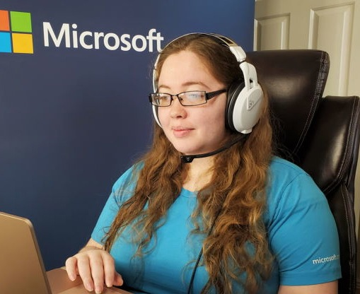Chelsea Cox sits at her home office and talks to a customer on her laptop.