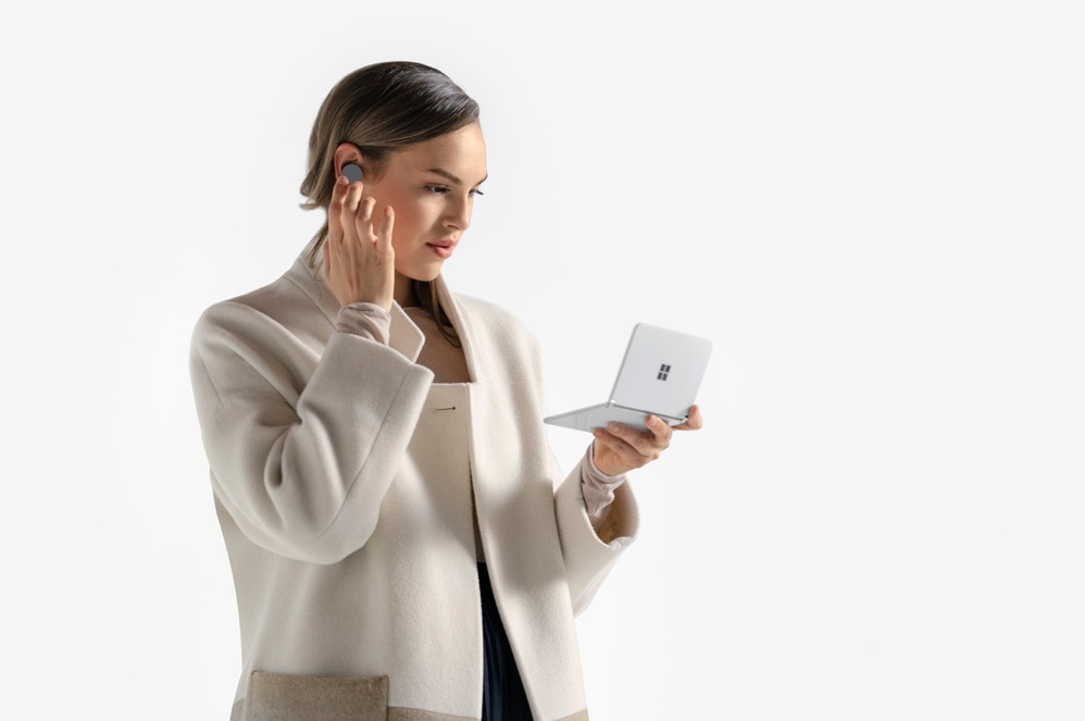 A person holding a Surface Duo in one hand and touching the Surface Earbuds in their ear with the other hand.