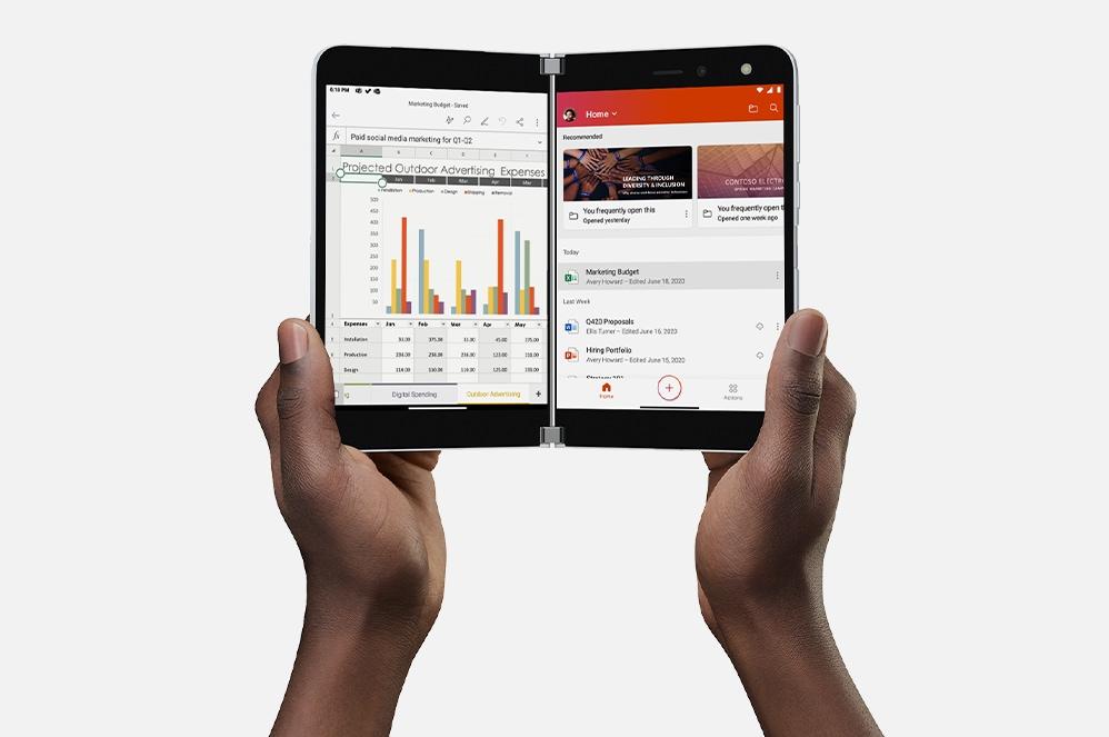 La mano de una persona sujeta un Surface Duo abierto.
