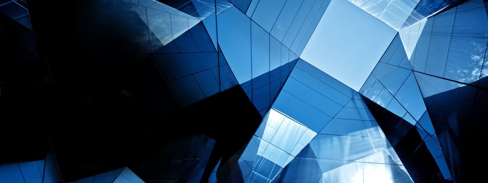 Die Fenster eines Bürogebäudes reflektieren den blauen Himmel