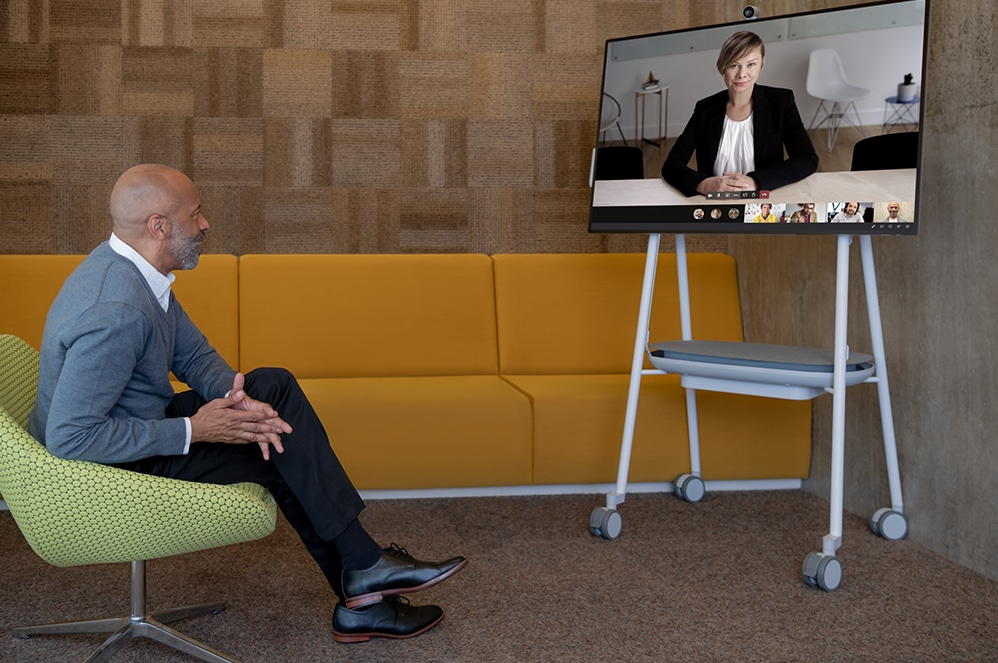 A man in an office talks with another person using the video call features on Surface HUB 2S.