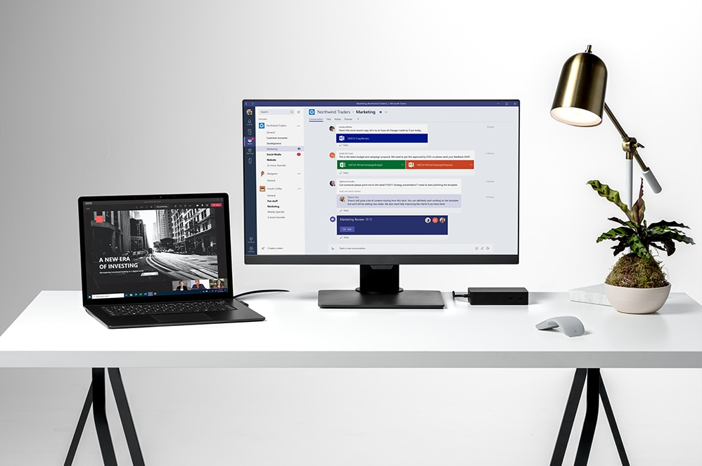 Surface Laptop 4 for Business on a desktop surrounded by a monitor, notebook, mouse and coffee mug.