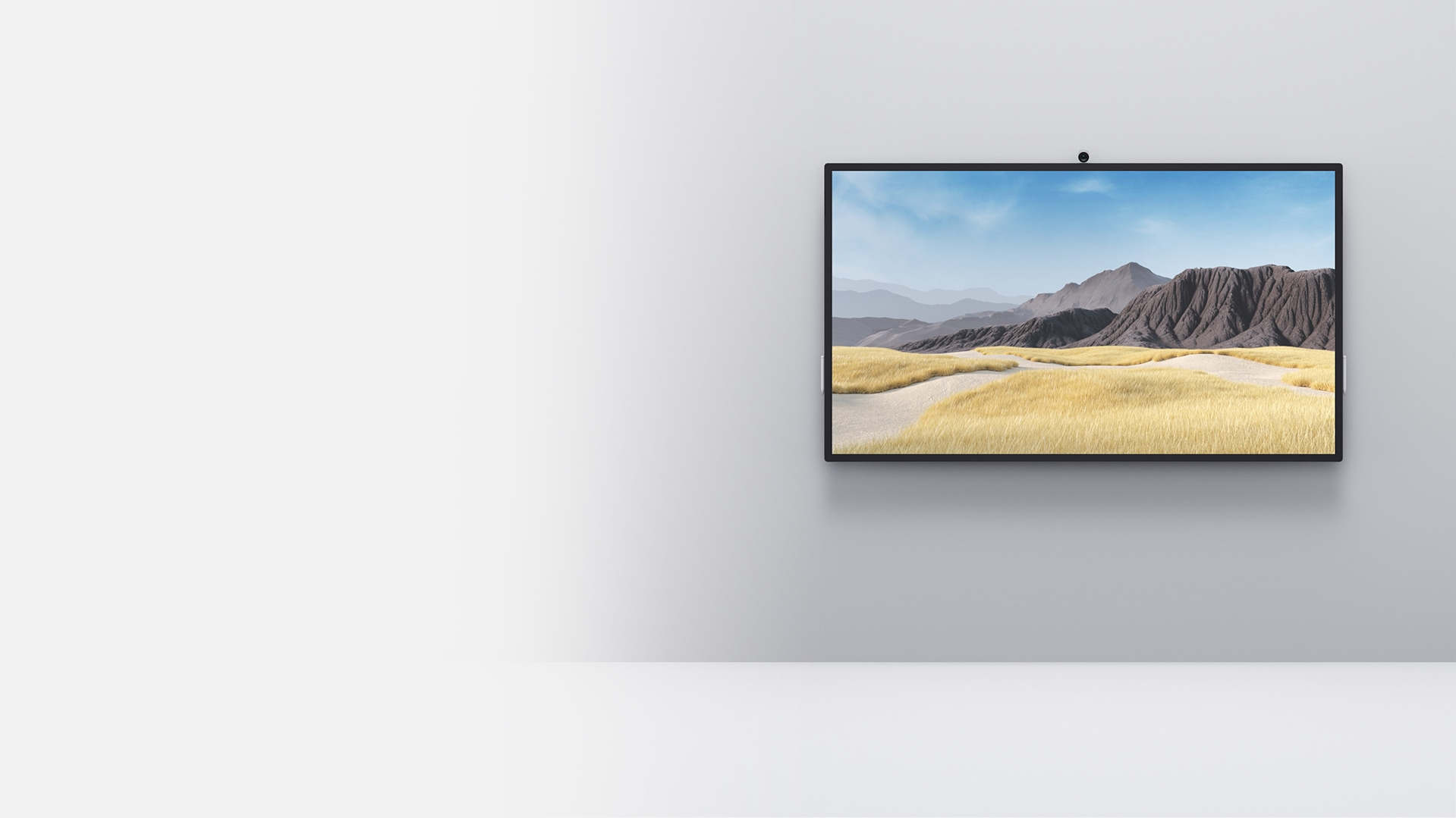 A Surface Hub 2S in the 85-inch size is shown mounted on a wall with two stools placed on each side of the device