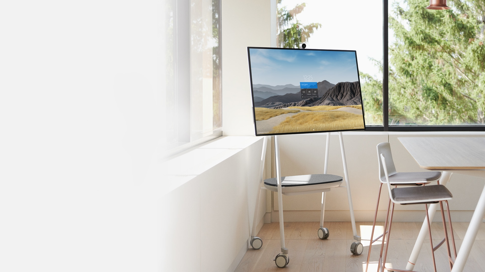 A Surface Hub 2S in the 50-inch size is shown in an office setting