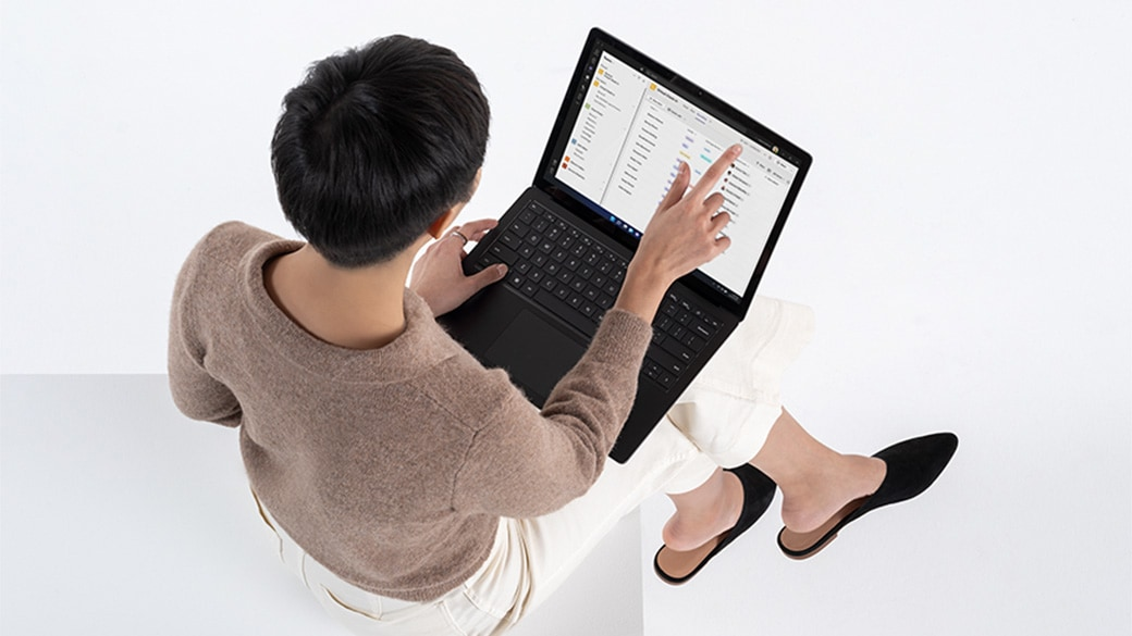 A top down view of a woman interacting with the keyboard on a Surface Laptop 4 in her lap