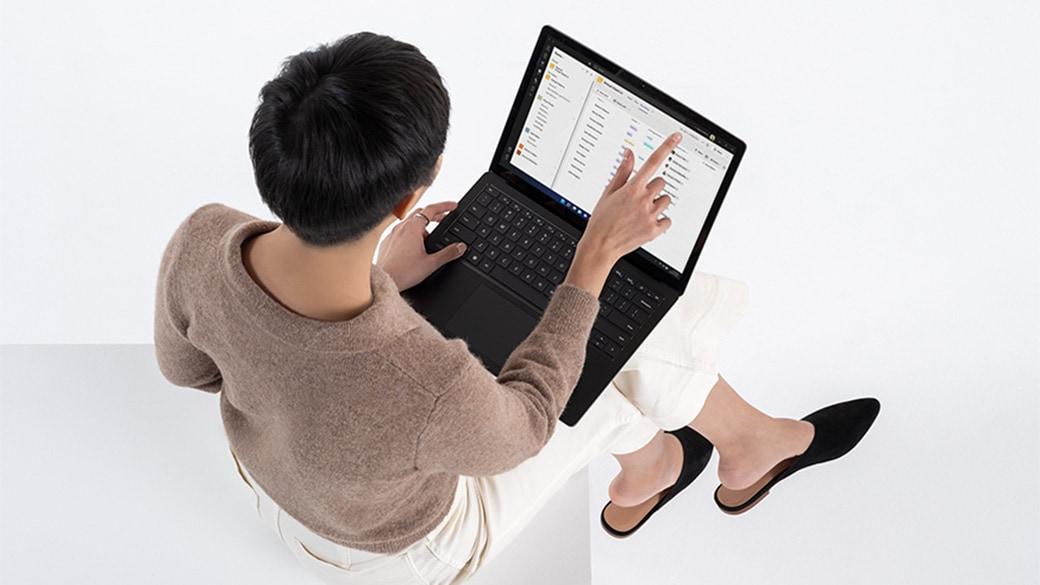 Ansicht einer Frau von oben, die mit der Tastatur eines Surface Laptop 4 auf ihrem Schoß interagiert