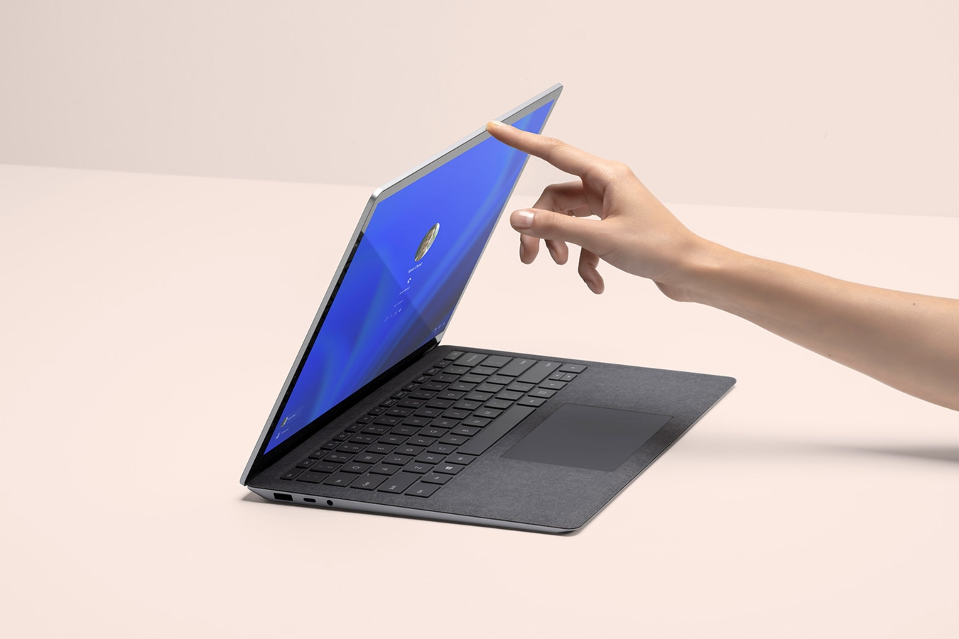 A person's hand is shown lifting the lid of a Surface Laptop 4, with the sign-on screen shown
