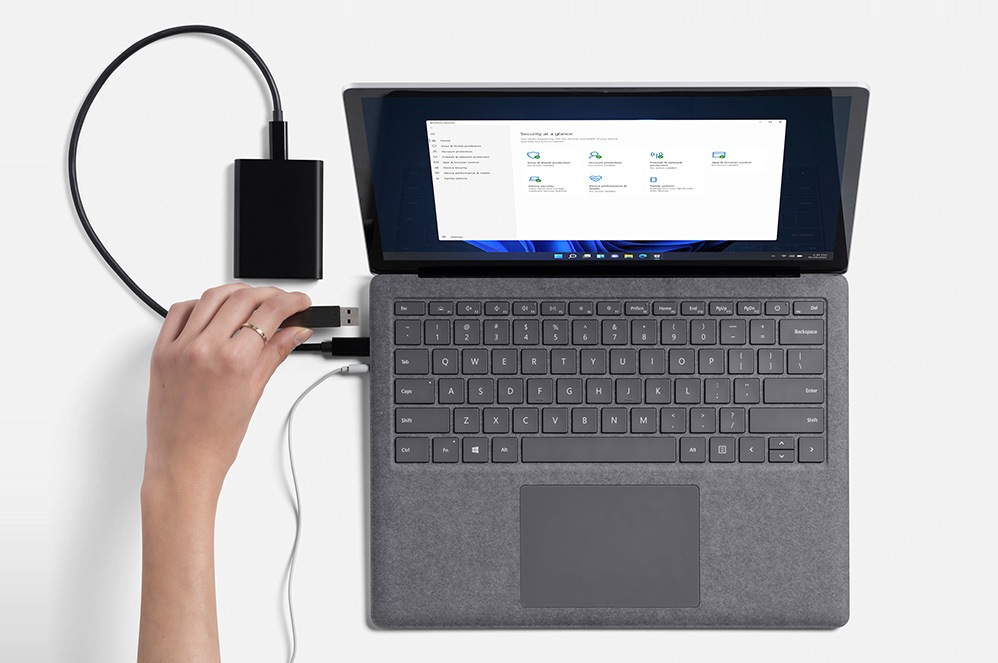 A person's hand is observed plugging in an external hard drive on Surface Laptop 4