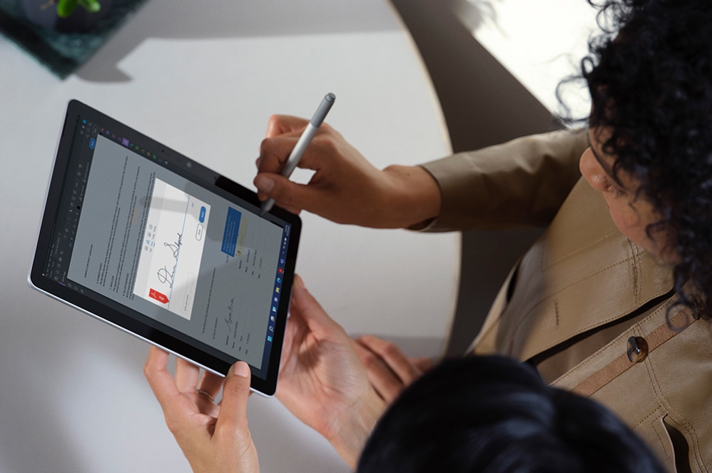 Two people interact in an office space while one person inks on a Surface Pro 7+ device.