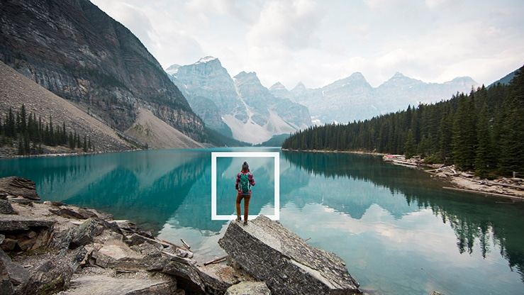 A person standing in front of a crystal blue lake surrounded by forest and mountains