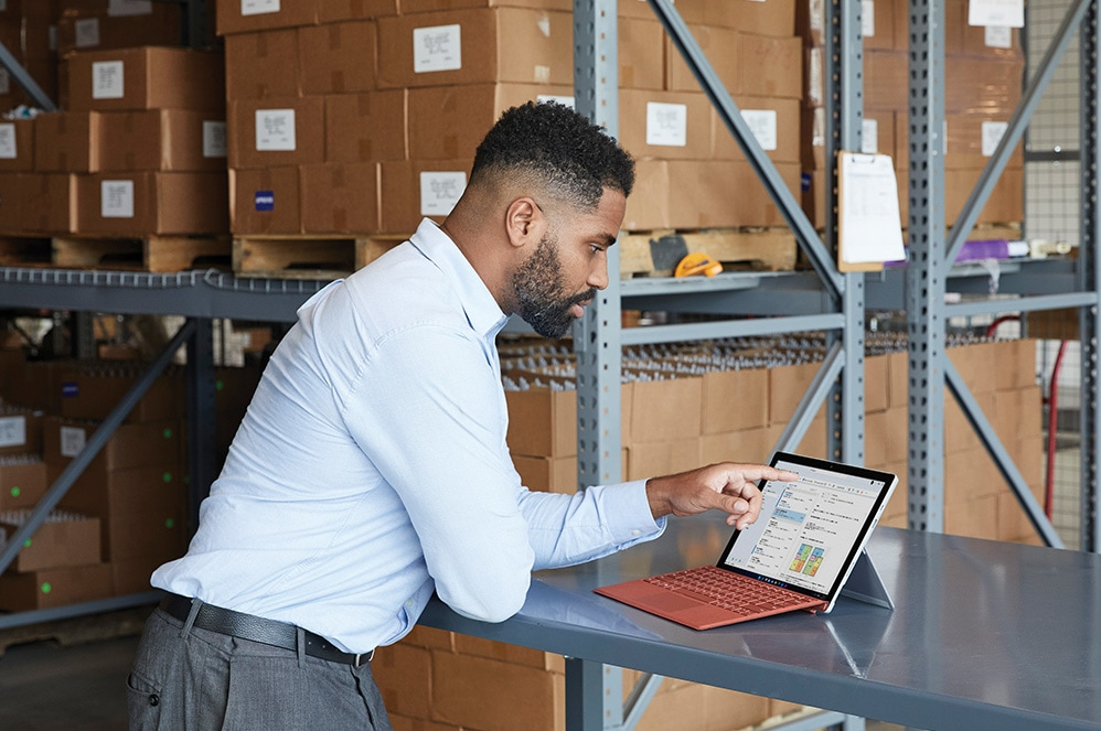 Surface Pro 7+ is pictured on a home office desk with Surface Pro X Signature Type Cover attached, Surface Pen and Surface Arc Mouse all in Poppy Red color.