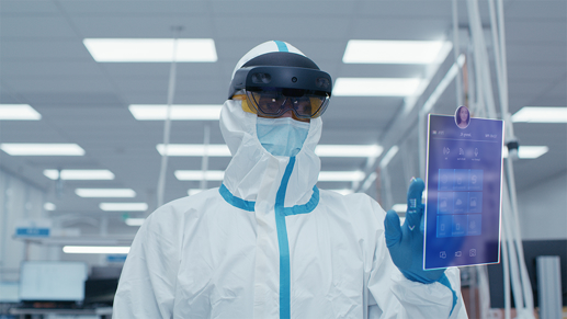 A person wearing PPE using a Holo Lens 2 to view an app in front of them.