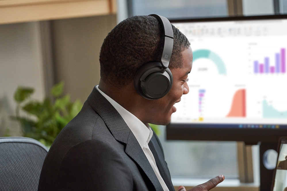 A person is seen wearing Surface Headphones 2 while viewing a Microsoft PowerPoint presentation on an external monitor