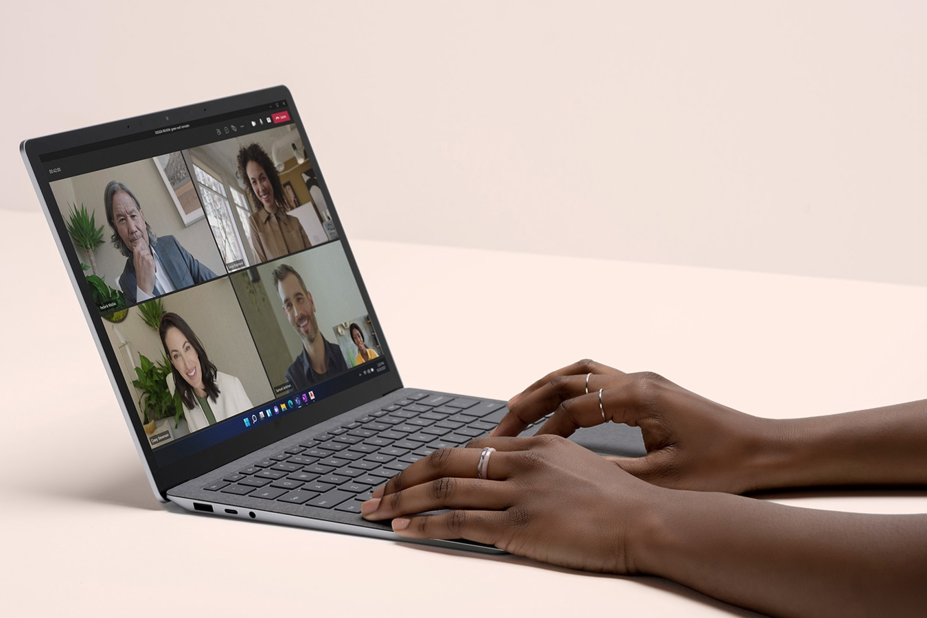 Microsoft Teams is observed on the screen of a Surface Laptop 4 device, with a person's hands laid down on the keyboard