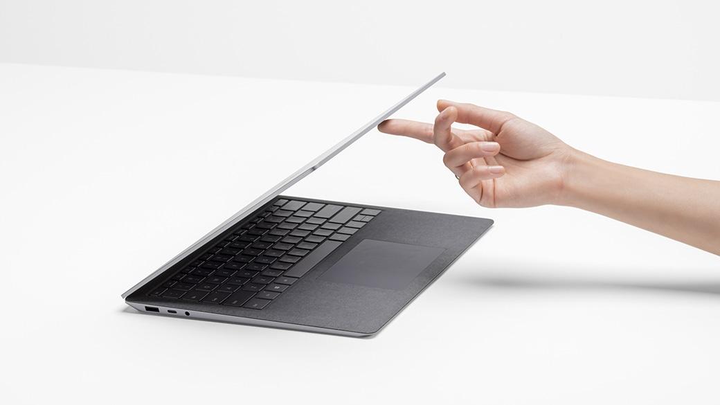 Eine Person hebt den Deckel eines Surface Laptop 4 mit einem Finger mühelos an