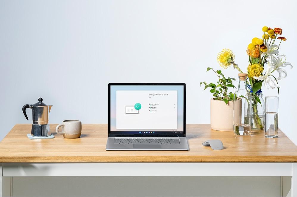 Surface Laptop 4 auf einem Schreibtisch mit Blumen rechts daneben.