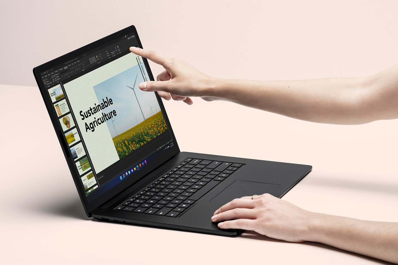 A person's hands are shown interacting with the touchscreen on Surface Laptop 4