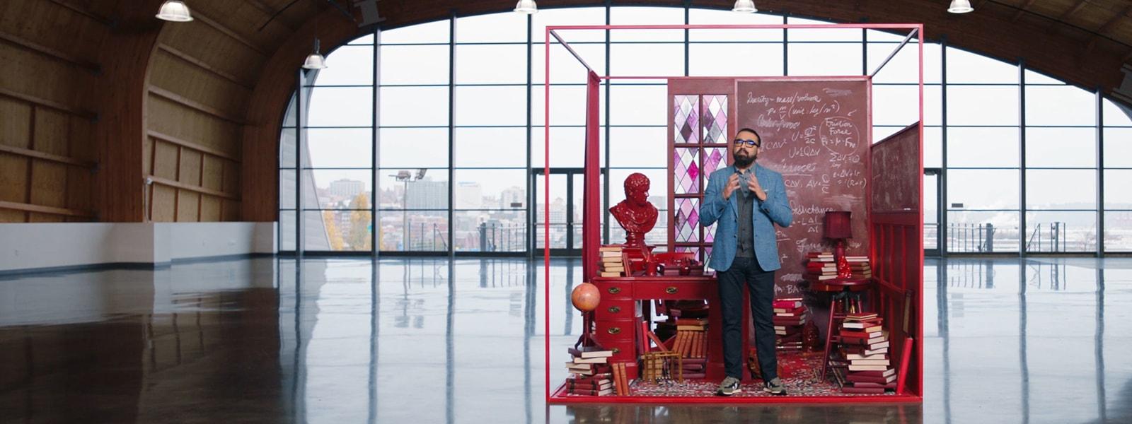 Gurdeep Pall, vicepresidente corporativo de IA empresarial de Microsoft, parado en un gran hangar con un cubículo rojo estilizado