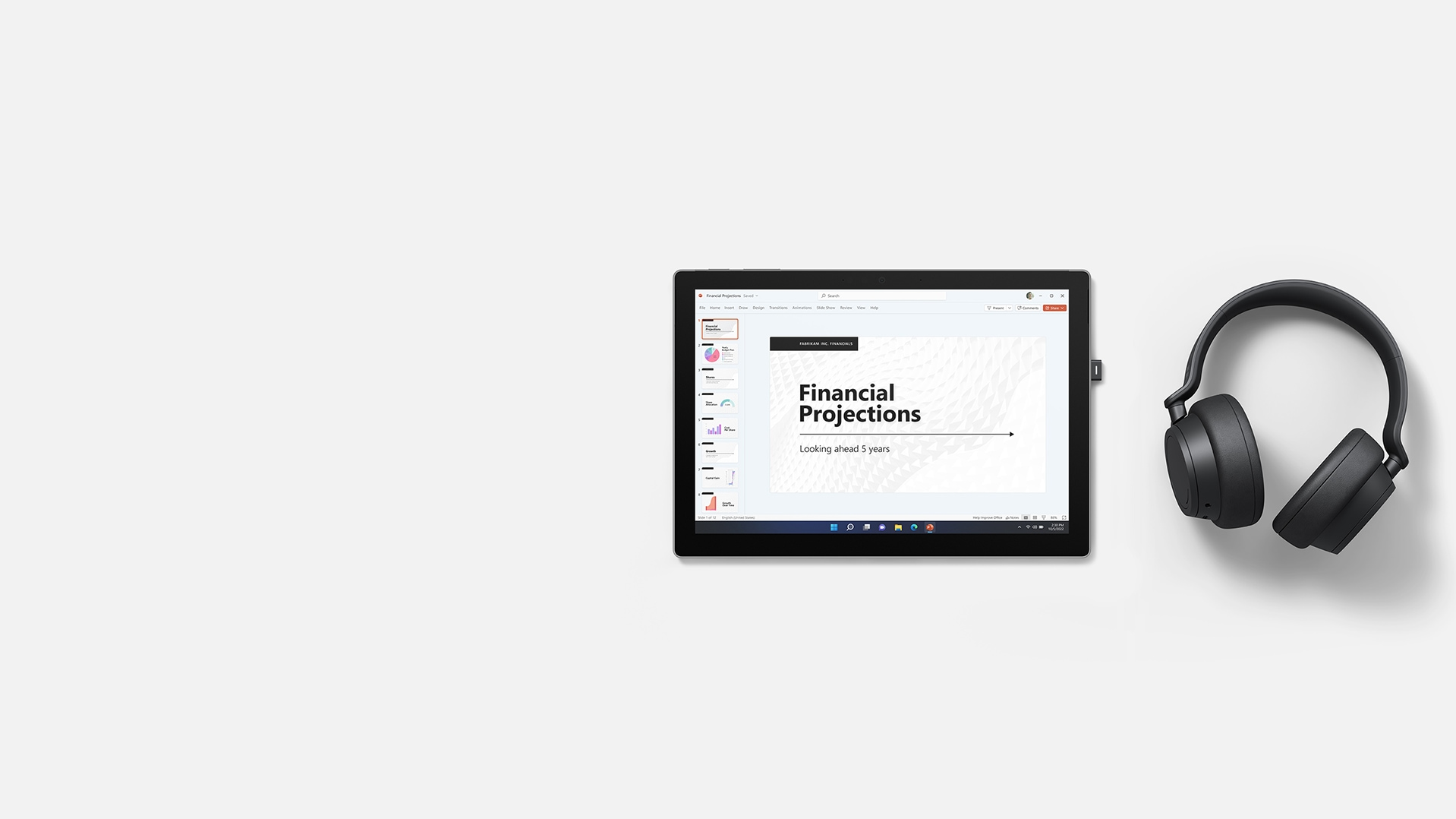 A Microsoft PowerPoint presentation on a Surface Pro 7+ with Surface Headphones 2+ placed on the right side