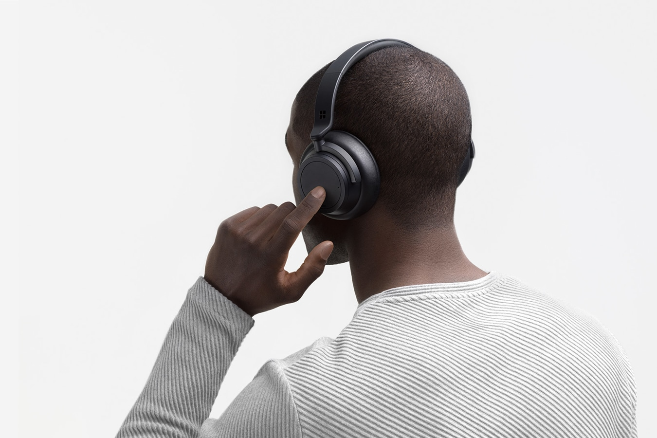 A person wears Surface Headphones 2+ and is shown using touch controls