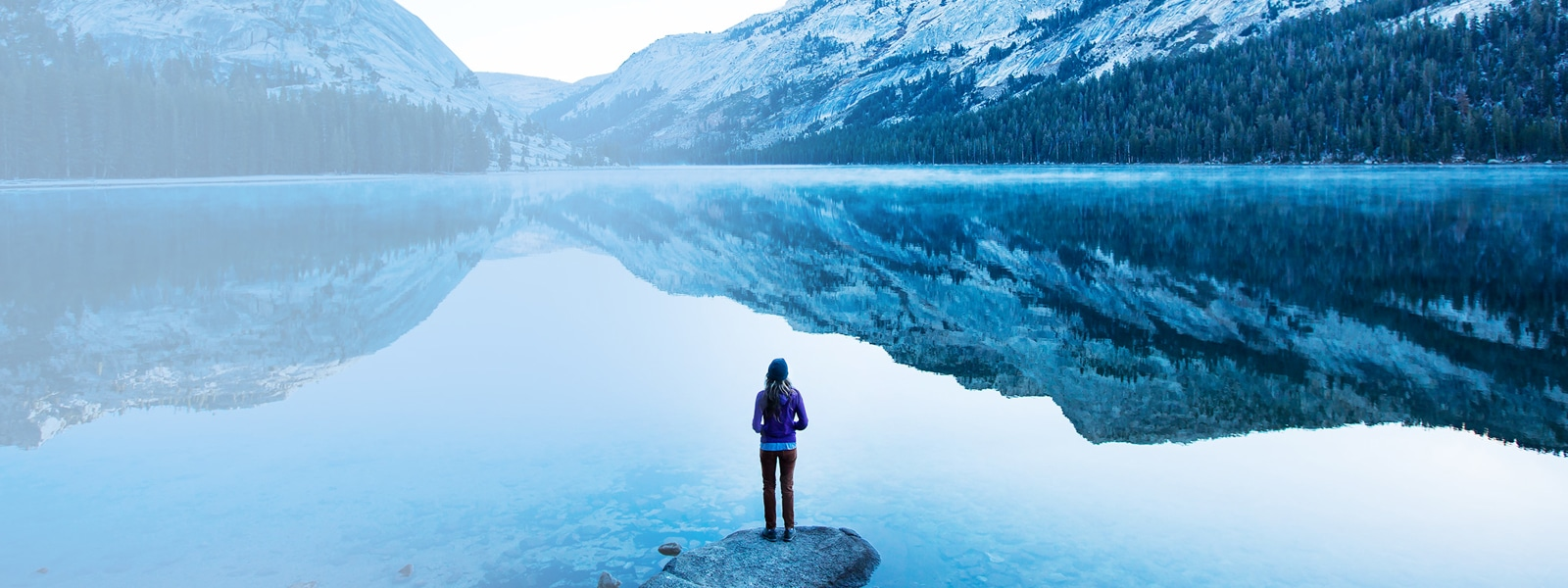 Woman stands on the shore of a lake surrounded by snowy mountains