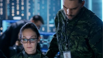 Two military personnel in uniform looking at a device together.