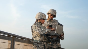 Two military personnel in uniform using a laptop together.