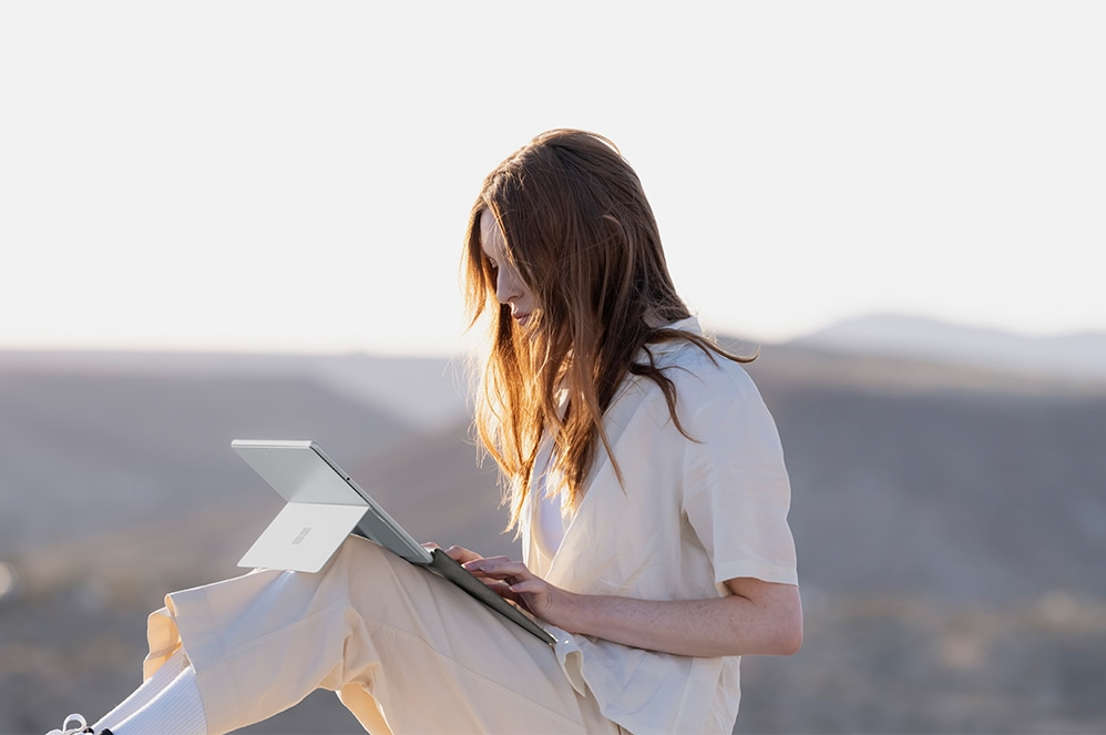 A person seated outdoors working with a Surface Pro device and Surface Pro Signature Keyboard for Business on their lap.