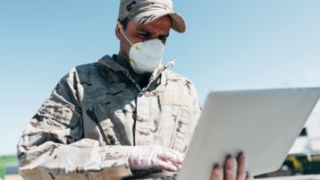 A member of the military in uniform and wearing a mask using a laptop.