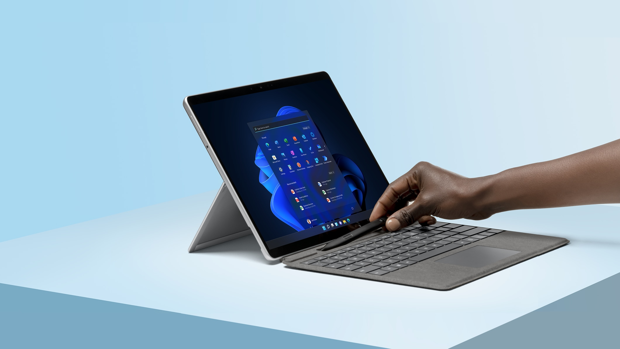 A person's hand removing Surface Slim Pen 2 for Business from Surface Pro Signature Keyboard with Surface Slim Pen 2 for Business attached to a Surface Pro device.