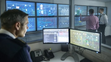 Three military personnel in a command center with many screens.