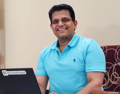 Venkatraman smiles at he sits in front of his laptop at his desk in his home office.