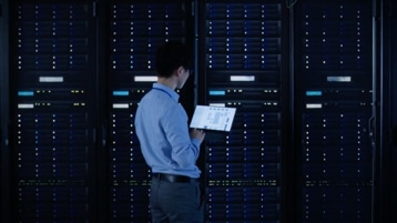 A person standing in a server room looking at a tablet device.