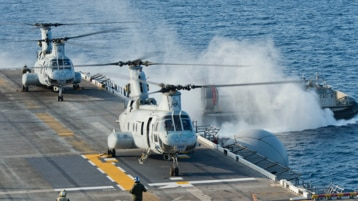 Two military helicopters on an aircraft carrier in the ocean.