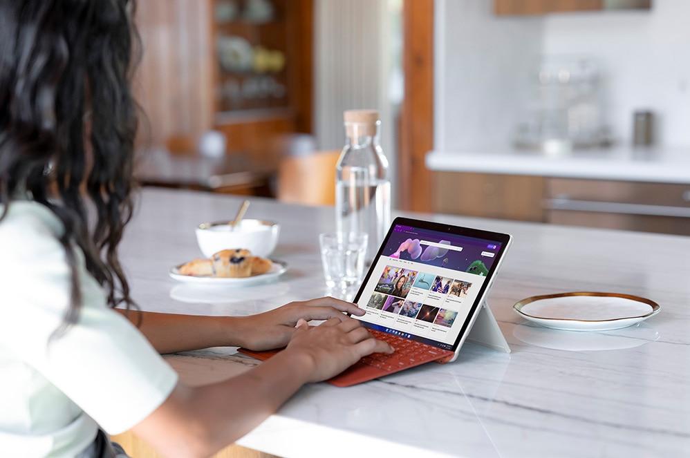 Enfant utilisant une SurfaceGo3 sous forme d'ordinateur portable sur un comptoir de cuisine.