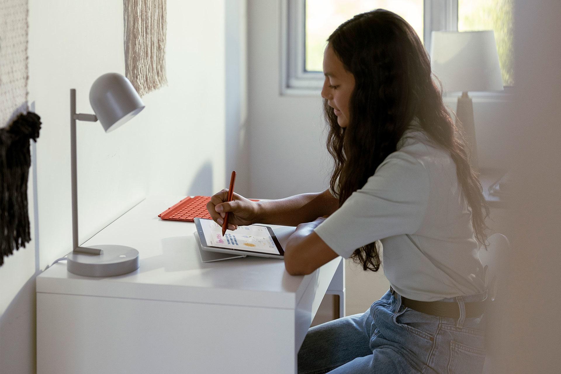 Enfant utilisant une SurfaceGo3 et un stylet Surface pour prendre des notes en cours.