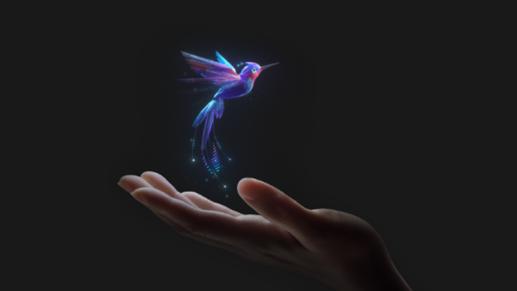 A hand holding up a virtual hummingbird.