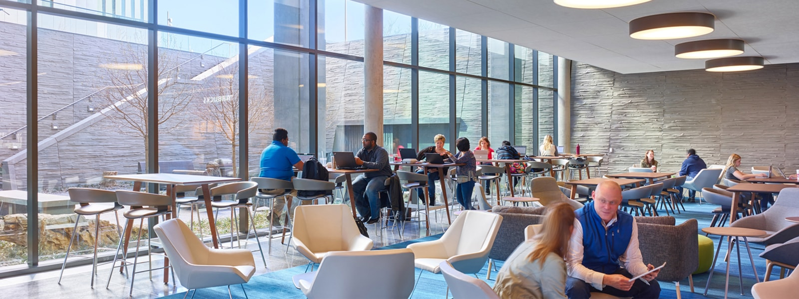 A cafeteria in an office with many people working in comfortable chairs and at tables.