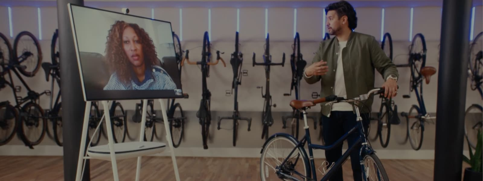 A bicycle shop employee showing a customer a bicycle over a Teams call on a Surface Hub.