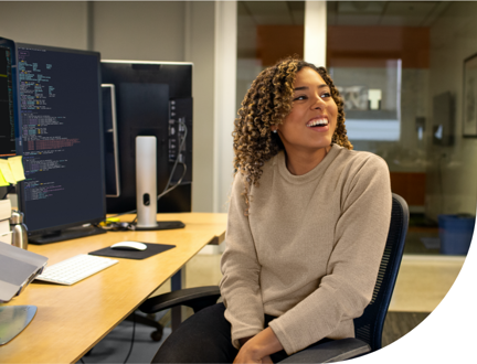 A person smiling sitting at their desk.