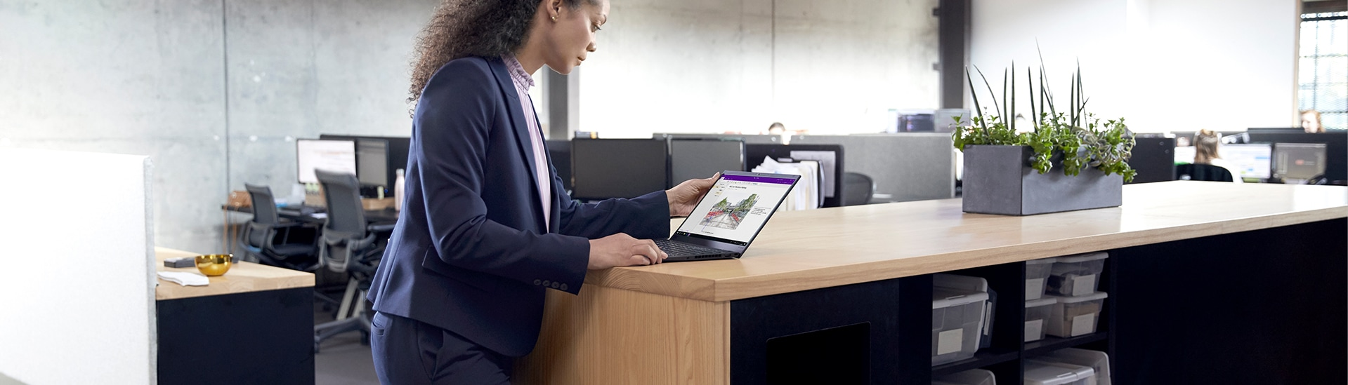 Photograph of a person standing at a counter-height table in a large, open office space looking at a laptop