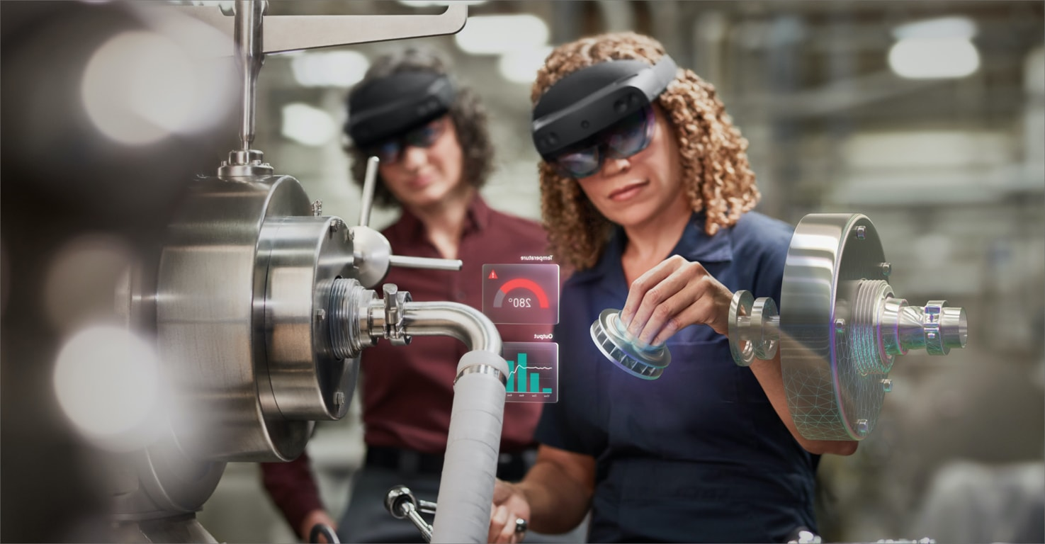 Two people using HoloLens 2 while working on a machine.