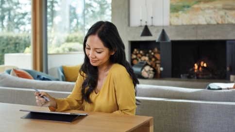 Person sitting in their living room using a Surface Pro tablet and holding a pen