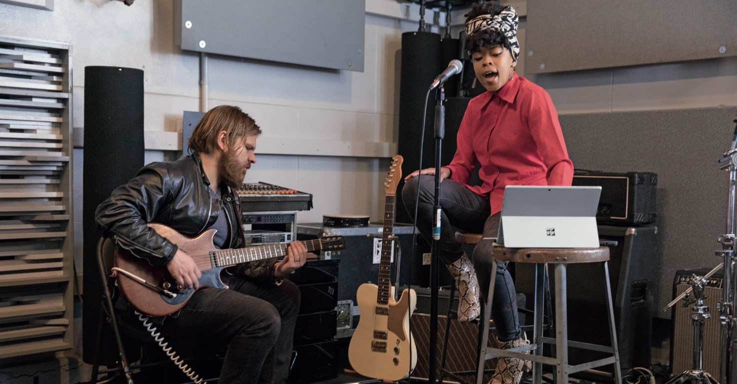 A guitar player and a vocalist playing music together in a studio  while using a tablet.
