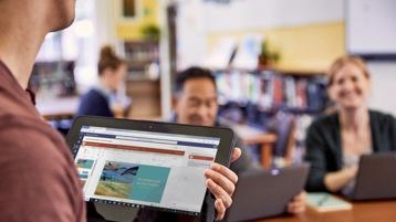 Ein Mann in einem Meeting hält ein Gerät in der Hand, auf dem Microsoft Teams zu sehen ist.