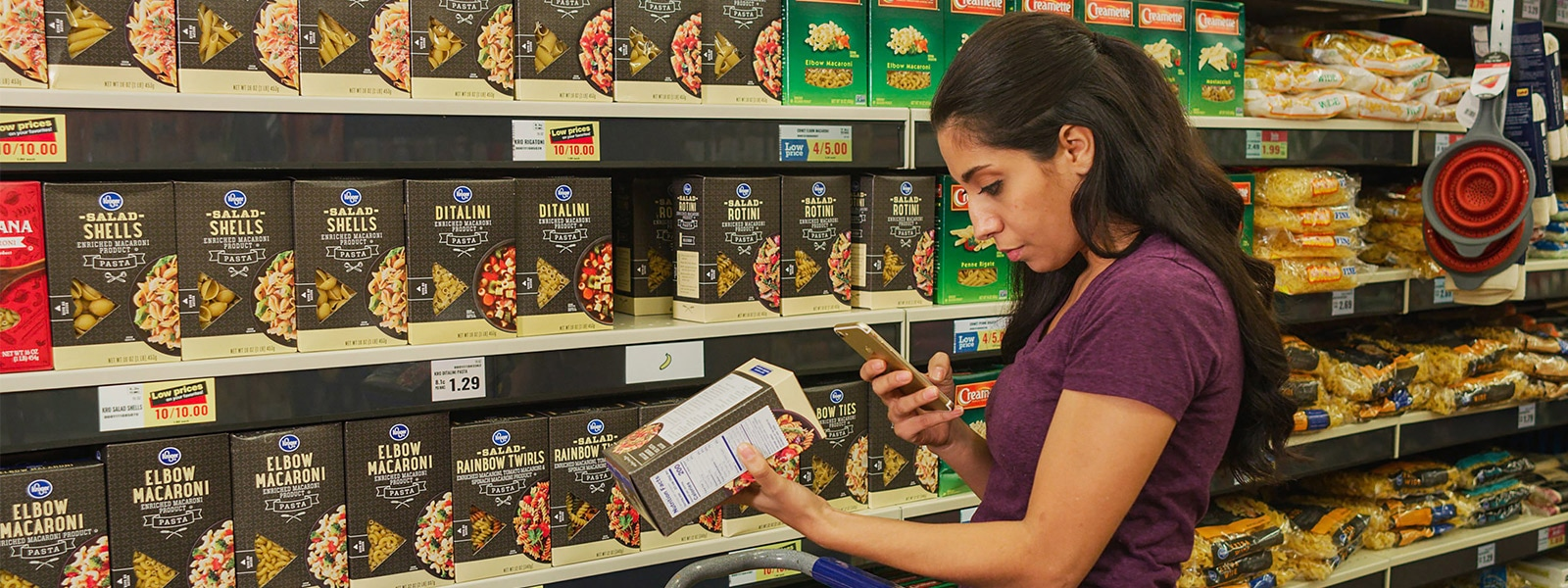 Woman using mobile device to scan grocery item